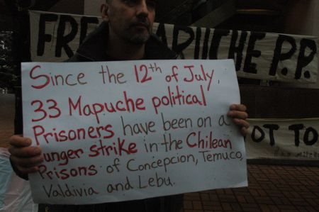Claudio Escobar with a sign in support of the Mapuche hunger strikers