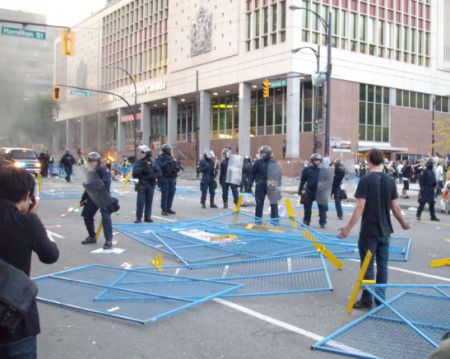 Riot cop advance blocked by dismantled fencing