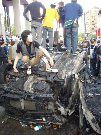 Canucks fans pose on overturned burned out car