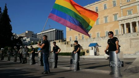 A defiant marcher waves the Pride flag in front of the Greek Parliament