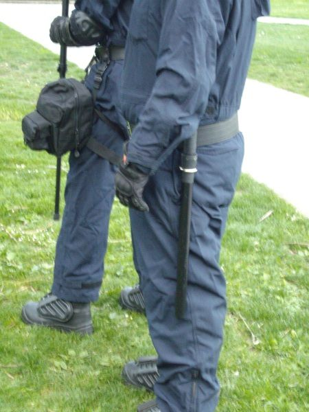 This second deployment saw PSU members wearing coveralls with body armour, 3 foot long riot batons, and gas masks strapped to their legs.