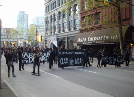 Marching east on Hastings Street carrying torches.