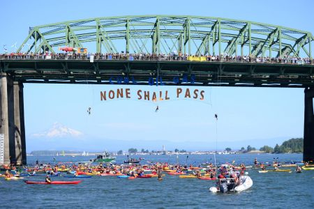 """Rising Tide repelled off a bridge in Washington State to oppose an approved oil export terminal. Banner says, """"Coal, Oil, Gas. None Shall Pass."""""""
