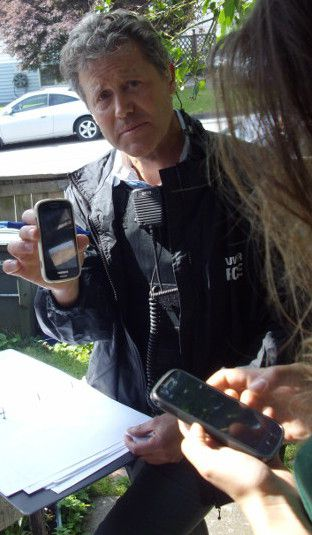 VPD detective constable Rainey holding a phone stolen by cops during June 3, 2014 raid.