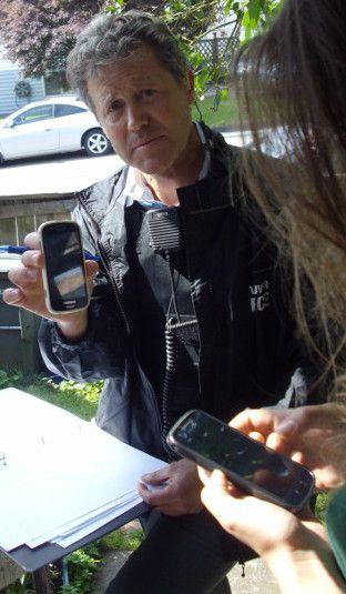 VPD detective constable Rainey holding a phone stolen by cops during June 3, 2014 raid.