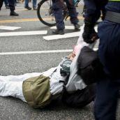 Riot Police drag an activist away