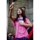 A First Nations women holds up an eagle feather in memory of those who have passed