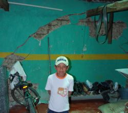 Child in front of cracked infrastructure to house.  His family claims the cracks were caused by blasts from the mine.
