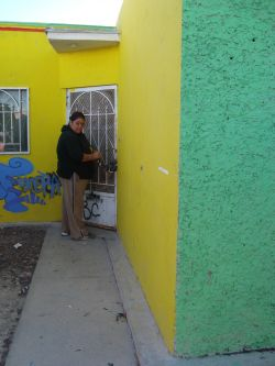 Sylvia, a community member in Villas de Salvarcar, opens the door to an abandoned house which the community reclaimed as a library 