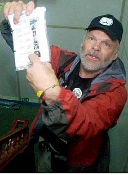 """As the aid ship is under attack, Kevin Neish holds up a """"hit list"""" found in an Israeli commando's backpack. Photo: Iara Lee"""
